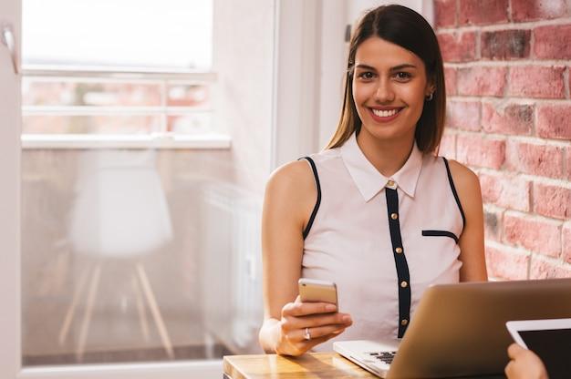 Sorrindo, jovem, executiva, enviando, um, mensagem texto, em, escritório lar