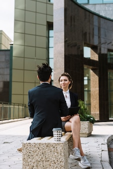 Sorrindo, jovem, executiva, olhar, homem negócios, sentar-se banco, frente, edifício escritório