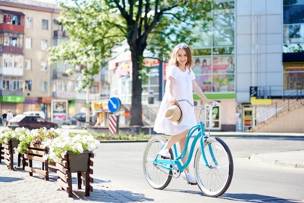 Sorrindo jovem fêmea no vestido branco, andar de bicicleta azul na frente dos edifícios da cidade moderna em dia de verão