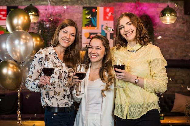 Sorrindo, jovem, femininas, amigos, em, bar, desfrutando, bebidas