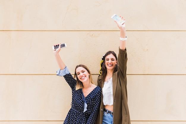 Sorrindo, jovem, femininas, amigos, levantando mão, segurando, telefones móveis