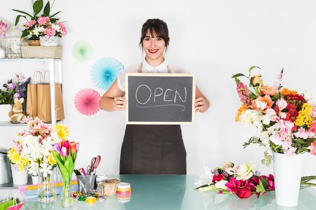 Sorrindo, jovem, femininas, florista, mostrando, ardósia, com, palavra aberta