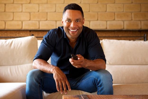 Sorrindo, jovem, homem americano africano, sentar sofá, e, observar tv