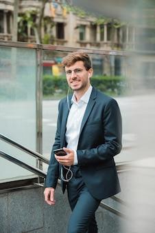 Sorrindo, jovem, homem negócios, com, seu, earphone, em, orelha, segurando, telefone móvel, em, mão