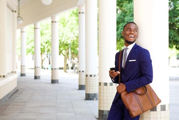 Sorrindo, jovem, homem negócios fica, com, telefone pilha, ao ar livre