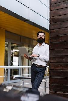 Sorrindo, jovem, homem negócios, segurando, laptop, em, mão, inclinar-se, parede
