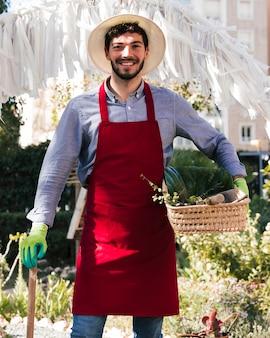 Sorrindo jovem jardineiro masculino no avental segurando cesta e ferramentas