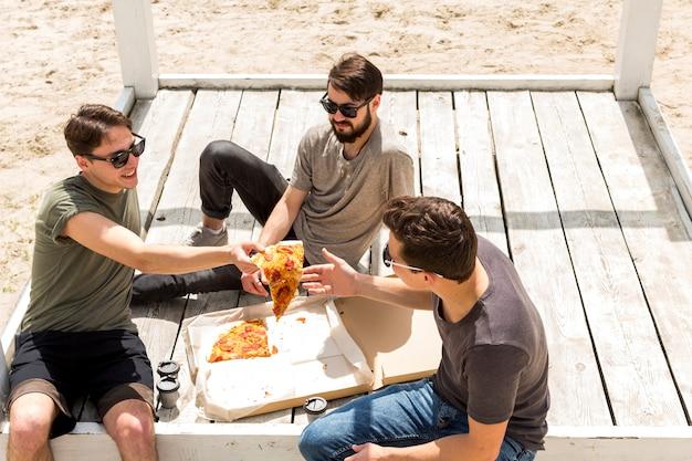 Sorrindo jovem macho dando fatia de pizza amigo na praia