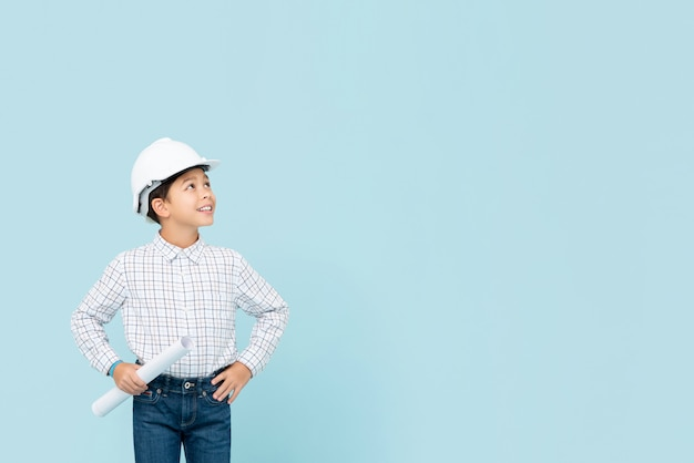 Sorrindo, jovem, menino asiático, aspirando, ser, futuro, engenheiro, segurando, capacete branco, e, blueprint, olhando copyspace