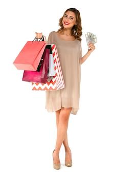 Sorrindo jovem morena de vestido segurando dinheiro dólares, posando com sacos de compras