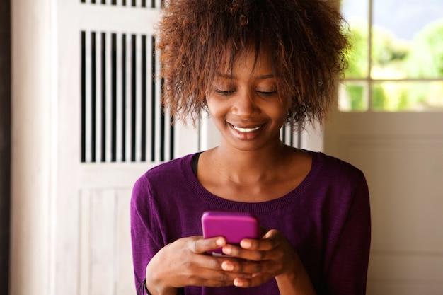 Sorrindo, jovem, mulher africana, olhar, telefone pilha