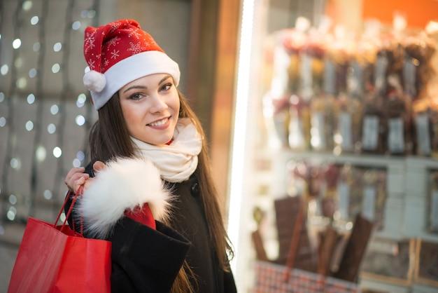 Sorrindo jovem mulher às compras em uma cidade antes do natal