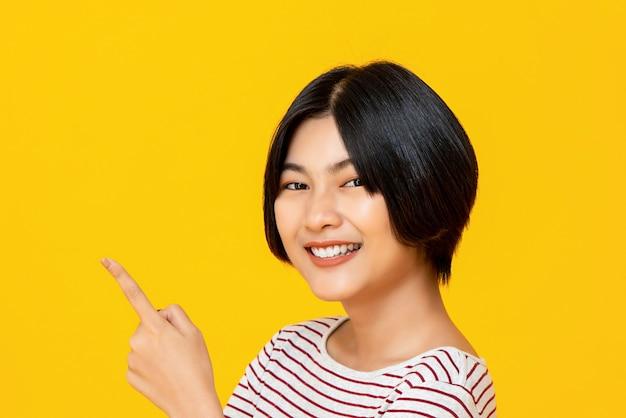 Sorrindo jovem mulher asiática, apontando a mão para o espaço vazio