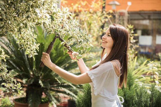 Sorrindo jovem mulher cortando folhas com tesoura de jardinagem