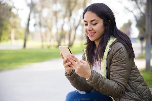 Sorrindo jovem mulher mensagens de texto sms no smartphone