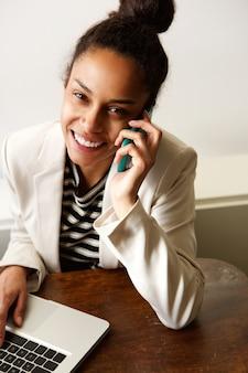 Sorrindo, jovem, mulher negócio, usando, telefone móvel, e, laptop