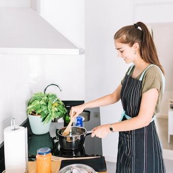 Sorrindo jovem mulher preparando comida na panela no fogão elétrico