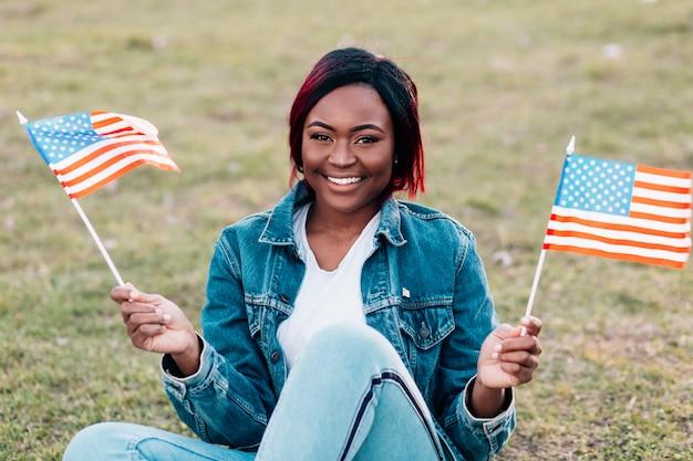 Sorrindo, jovem, mulher preta, com, bandeiras americanas