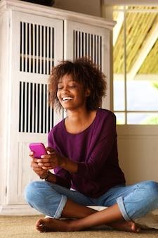Sorrindo, jovem, mulher preta, sentar chão, com, telefone pilha