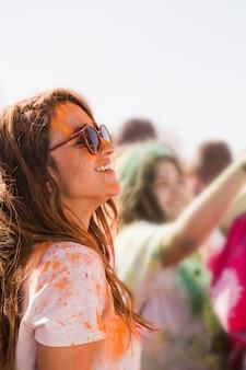 Sorrindo jovem mulher usando óculos de sol bagunça com um pó de holi laranja