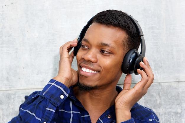 Sorrindo jovem negro com fones de ouvido, ouvindo música