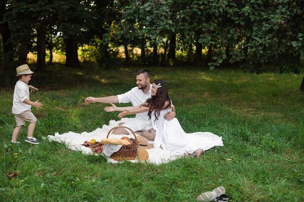 Sorrindo, jovem pai e mãe descansando sobre a manta no parque enquanto seu filho pequeno corre para seus braços. família e conceito de lazer