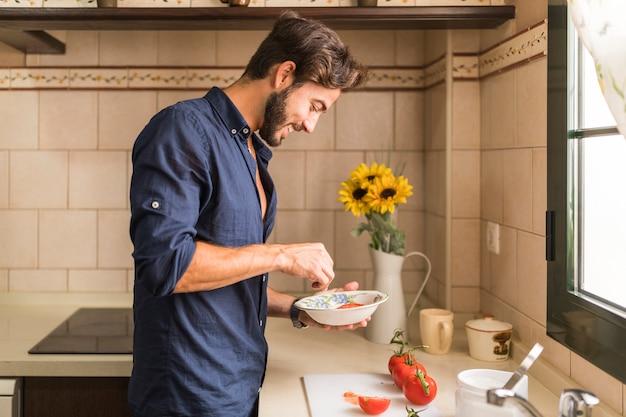 Sorrindo jovem preparando salada na cozinha