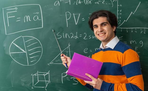 Sorrindo, jovem professor de geometria em frente ao quadro-negro na sala de aula segurando um livro apontando com um ponteiro para o quadro-negro olhando para a frente