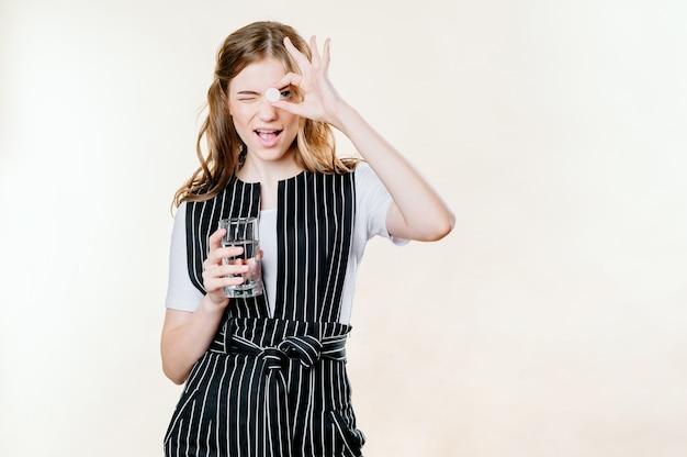 Sorrindo jovem saudável segurando um comprimido de copo de água