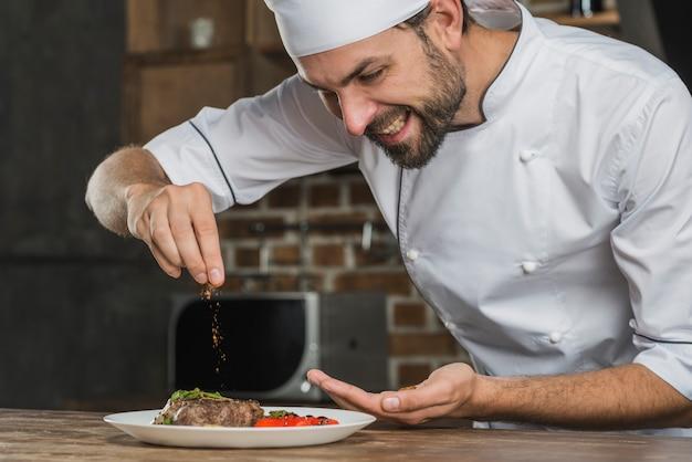 Sorrindo jovem tempero masculino especiarias sobre comida