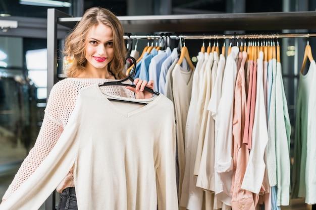 Sorrindo jovem tentando uma roupa nova em uma loja de roupa