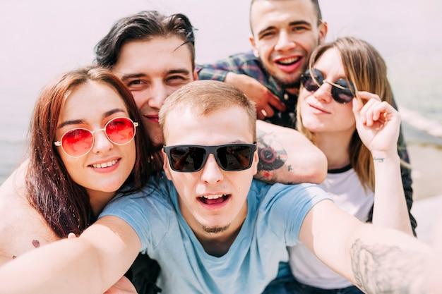 Sorrindo jovem tomando selfie com amigos