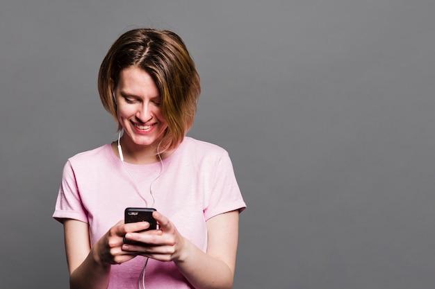 Sorrindo jovem usando telefone celular contra parede cinza