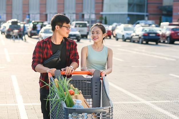 Sorrindo jovem vietnamita menino e menina carregando carrinho de mercado com alimentos diferentes perto de supermercado