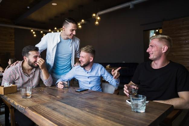 Sorrindo jovens amigos desfrutando no restaurante
