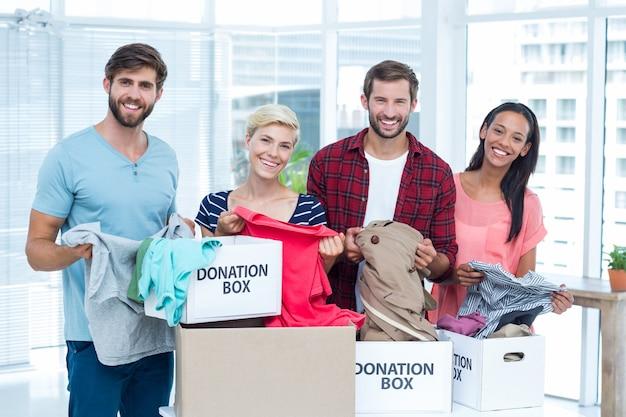 Sorrindo jovens amigos voluntários separando roupas