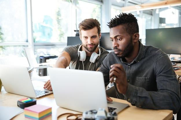 Sorrindo jovens colegas sentados no escritório de coworking usando laptop