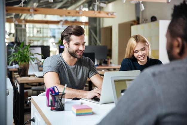 Sorrindo jovens colegas sentados no escritório de coworking