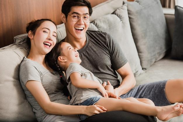 Sorrindo jovens pais e seu filho estão muito felizes, eles estão em casa