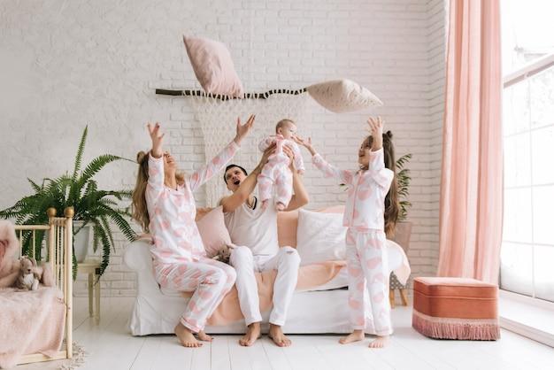 Sorrindo jovens pais, suas duas filhas se divertem em casa e jogam travesseiros em um interior luminoso
