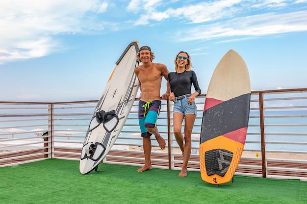 Sorrindo jovens surfistas ativos casal relaxando na praia após esporte com prancha de surf. estilo de vida saudável. esportes aquáticos extremos