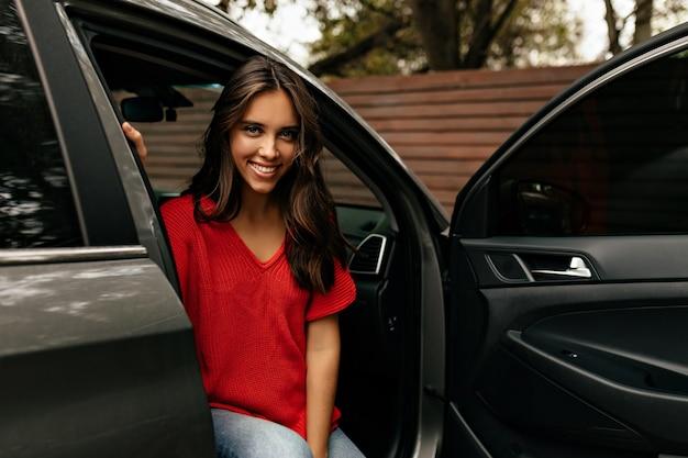 Sorrindo, linda deitada com longos cabelos ondulados, vestindo uma camisa vermelha, sorrindo, sentada no carro