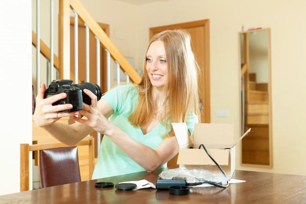 Sorrindo linda garota com loira desempacotando nova câmera digital