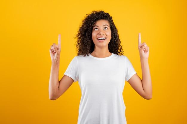 Sorrindo linda garota negra poiting dedos isolado sobre amarelo