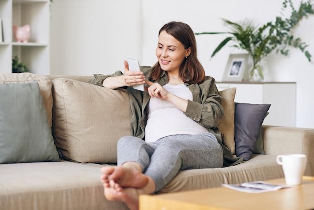 Sorrindo, linda jovem grávida em uma camisa casual, sentada no sofá e usando o smartphone enquanto lê artigos na internet sobre criação de bebês