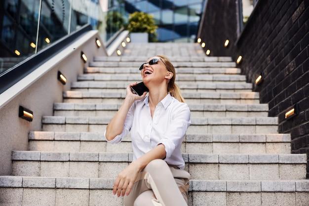 Sorrindo linda loira empresária na moda sentada na escada em frente ao centro de negócios e usando o telefone inteligente.