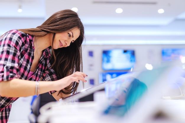 Sorrindo linda morena com cabelos longos, experimentando o novo tablet em pé na loja de tecnologia.