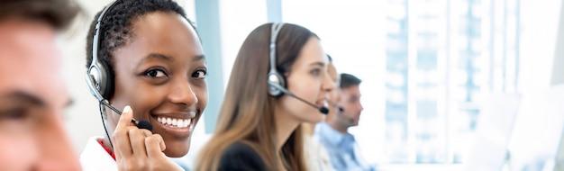 Sorrindo linda mulher afro-americana, trabalhando em call center com equipe diversificada