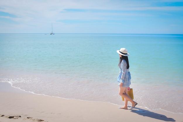 Sorrindo linda mulher asiática, vestindo moda verão andando na praia arenosa do oceano