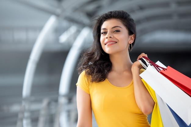 Sorrindo linda mulher carregando sacolas coloridas